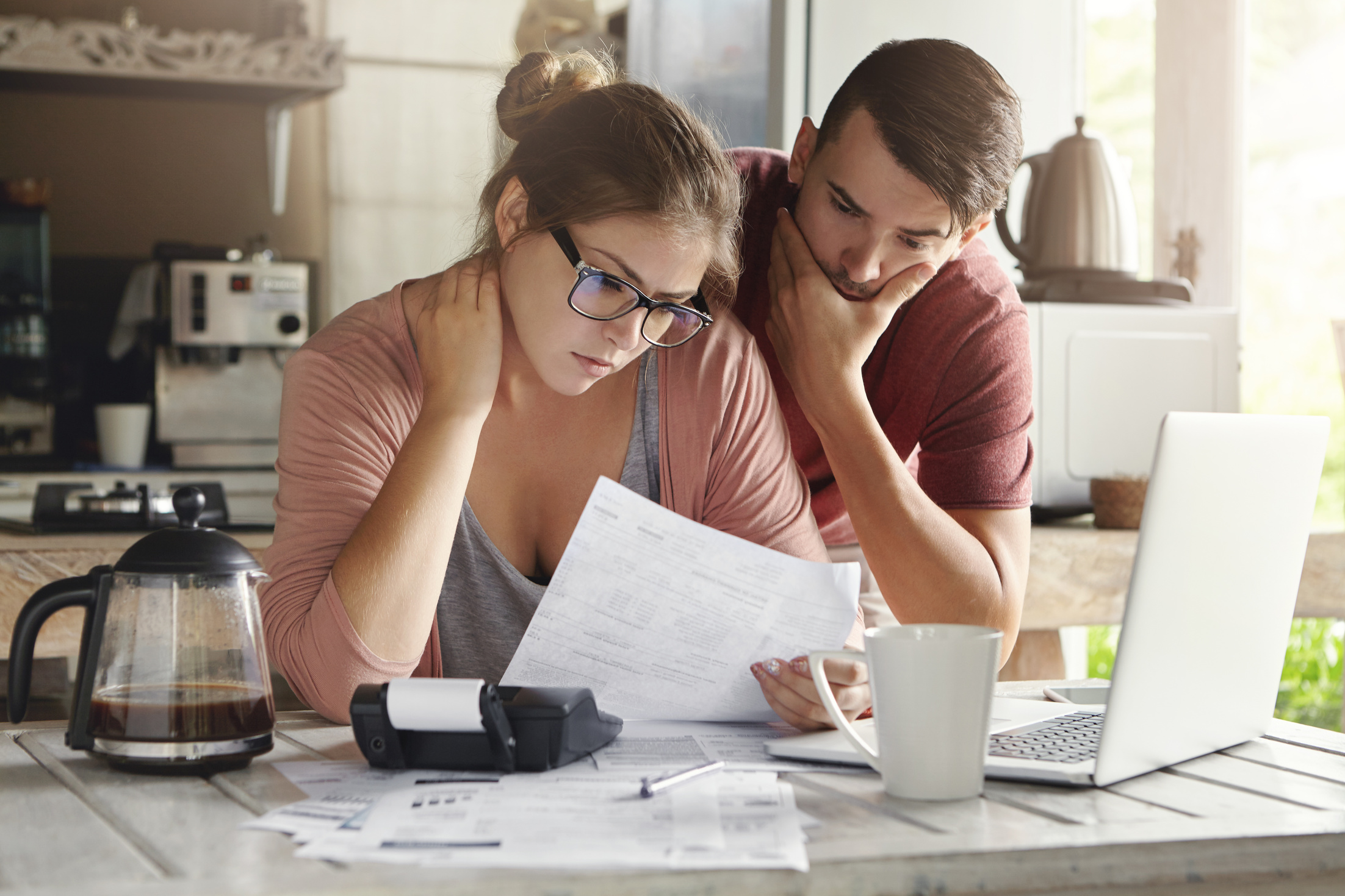 Young Caucasian family having debt problems, not able to pay out their loan. Female in glasses and brunette man studying paper form bank while managing domestic budget together in kitchen interior